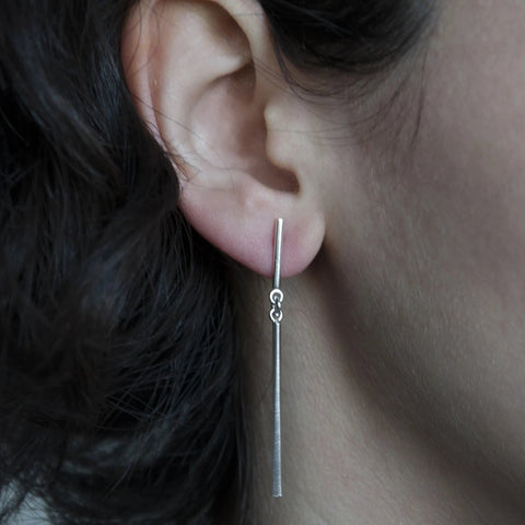 The Aldo earrings are a fun drop earring in sterling silver made of two simple lines connected by articulating rings. They measure about 30 mm (1.5'') long.