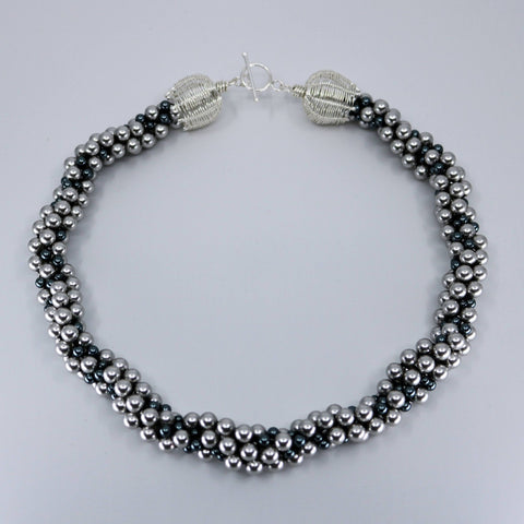 "Dot Necklace has about 8 separate strands of Swarovski pearls tightly braided in the Kumihimo technique. The sterling silver clasp is hand-made and can be worn as the centrepiece, off-centre, or to the back of this 19"" long fine necklace."