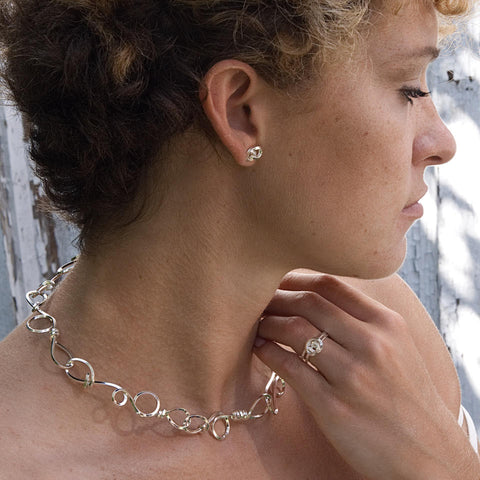 Short Knot necklace in bright sterling silver. Each piece is individually hand-fabricated, randomly forming the wire in its knot shapes by hand or with simple tools. Thus, every one of these necklaces is completely unique.