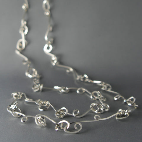 "Long Knot Necklace in bright sterling silver.  Each piece is individually hand-fabricated, embracing random forming of the wire to mimic plant-like growth. Each is completely unique. 89 x 2 cm/ 35 x 0.75""."