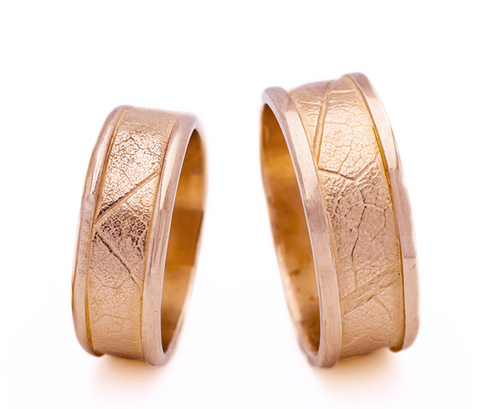 Rose-gold Maple Leaf Bands in 14k gold.  One pair is currently available in sizes 8 and 10, each sold separately.  These rings are inspired by my natural surroundings, and are created in celebration of my acquisition of Canadian citizenship. The imprint of real leaves from Maple trees is elegantly bordered by square rails or round rails. These sets make wonderful wedding bands.  Copper gives rose gold its reddish hue which fits well with the theme of Canada.  Dorothée