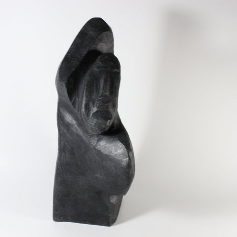 Spirits. The figures appear to be emerging from the depth of the  black soapstone with carving marks suggesting sweeping movement on the surface.   This sculpture by Joe Aulatjut, a carver based in Arviat, measures 25 x 12 x 12 cm.