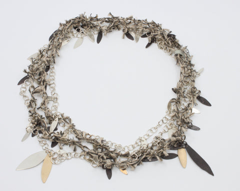 "A long linen thread neckpiece with small black leaves doubles the sterling silver link chain with silver and brass leaves. Wear together to experience the textural contrast or singly to enjoy the fineness of each. 42""/106 cm."