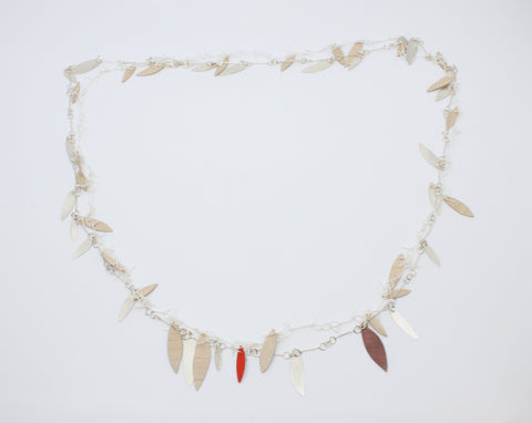 "A long, loosely-knotted  white linen thread neckpiece with birch plywood leaves, one painted orange is married to a sterling silver link chain with silver leaves--and one red copper leaf. Delicately balanced together, they can be worn singly. 42""/106 cm."