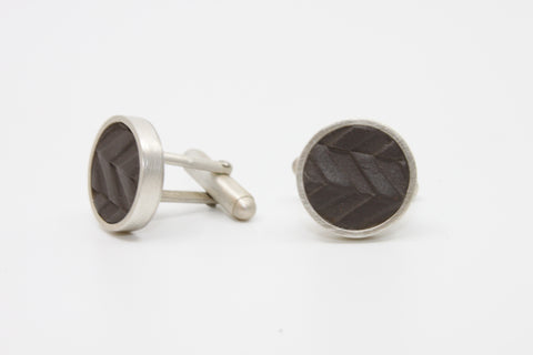 Tire-track cufflinks in black matte porcelain set in brushed sterling silver.