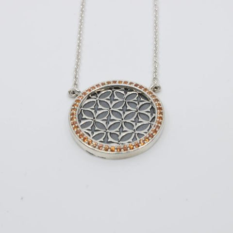 Necklace with pink sapphires set in sterling silver around a stamped pattern.