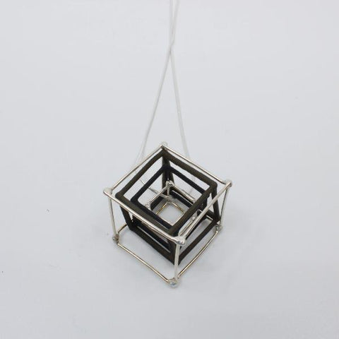 Nesting cube pendants in black nylon and sterling silver on snake chain.