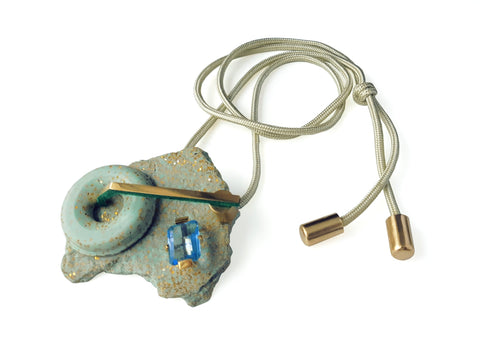 brooch or pendant on a brass-finished cord, the soft blue-green sculpture of glitter resin has flocking, steel and a large lab-grown blue stone and measures 6 x 7 x 2.5 cm.