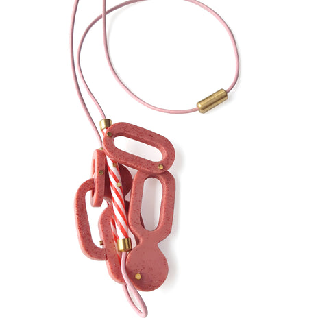 Strawberry Milkshake Necklace.  Large pink glitter resin components are riveted together with brass and capture a pair of red-striped plastic straws,  On a pink leather cord, the brooch measures 12 x 7 x 3 and hangs 42 cm in length.