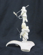 Hunters in the act of successfully harpooning fish, with happy baby in the hood. 10 x 4 x 4 cm, side view.