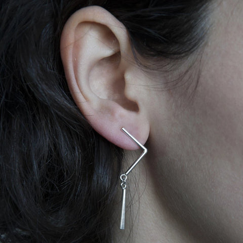 The Mimar earrings are a zigzag drop earring in sterling silver that swing gently just below the ear. They measure about 40 mm (1.6'') long.