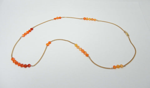 Delicate curb chain in 14k yellow gold with carnelian beads.