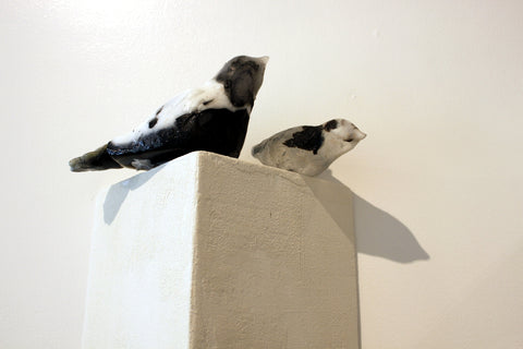 "Nesting, two cast glass bird sculptures on a ""rooftop"" wall unit of hand-made wood."