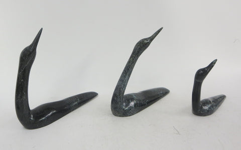 Three Loons, delicately carved soapstone sculptures viewed as the recognizable silhouette gracefully glide through the water.  Left: 18 x 15 x 4 cm, Centre: 17 x 15 x 4 cm, Right: 13 x 10 x 4 cm.  Ning Ashoona