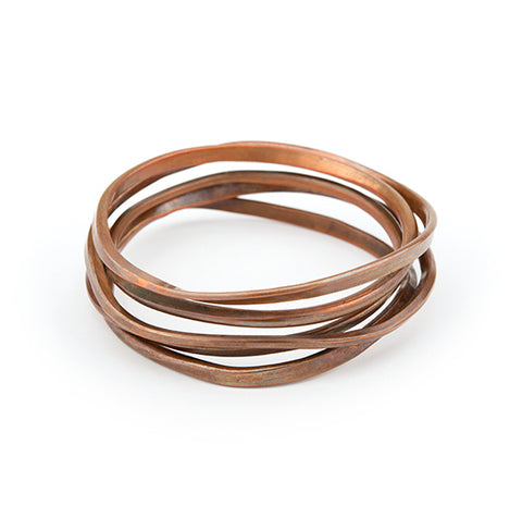 Onemeter Copper Bangle. As a companion piece to the Onefooter Ring, this bangle starts is one meter of copper wire forged to vary the line quality following the original brush and ink drawing.  Wound repeatedly into a continuous loop, without beginning or end.