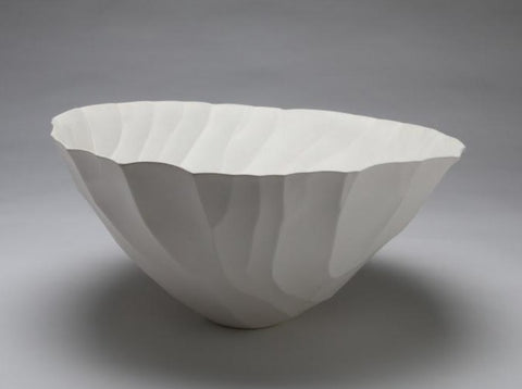"Swept.  This impressive white porcelain vessel suggests fragility but radiates a calm sense of beauty.  Thanks to the artist's original casting process that incorporates fibreglass and involves multiple firings, it is incredibly fine but internally strong, 2019, 40 x 40  x 19cm/16 x 16 x 7.5""."
