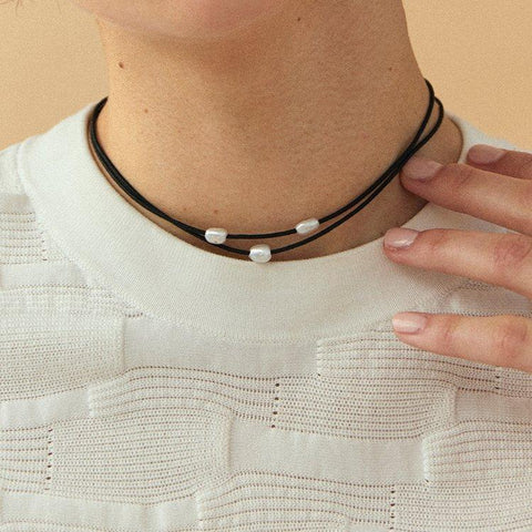 The Jupiter Choker is a necklace with 3 white freshwater pearls threaded on a black  waxed cotton cord that is water resistant and durable. It is closed at the back with a handmade sterling silver button. Meant to be worn close to the neck, the length is adjustable from 13.5'' to 14.5''.