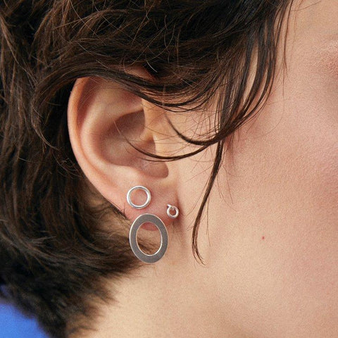 The Iris Studs are an open loop stud that sits flat on the ear. They are made in sterling silver and have a polished finish. They measure approximately 8 mm (5/16'') across.