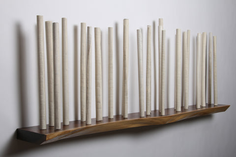 Sanctuary, sculpture of 25 porcelain torn-edged scrolls wall-mounted on a live edge walnut wall shelf.  52L x 8.5H x 21D in