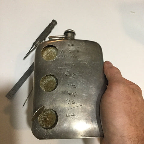 Flask With Portholes. An antique flask with names etched into its surface, stamped with date, has been altered to admit 3 portholes. Each porthole window is optical lens has been inserted into silver coins that have become their frames. These coin 'frames' are then drilled into and screwed with tiny bolts that must be tightened from within.
