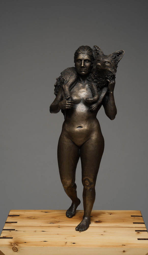 Diana's Stole, bronze with 200 year old reclaimed local wood. Edition 1 of 3 has sold; the artist could be commissioned to create a new sculpture.  Creating a moment of warmth and protection, a fox lies lazily across Diana's shoulders. It is a tender union between woman and animal, where the huntress and her prey make a pact of mutual survival.