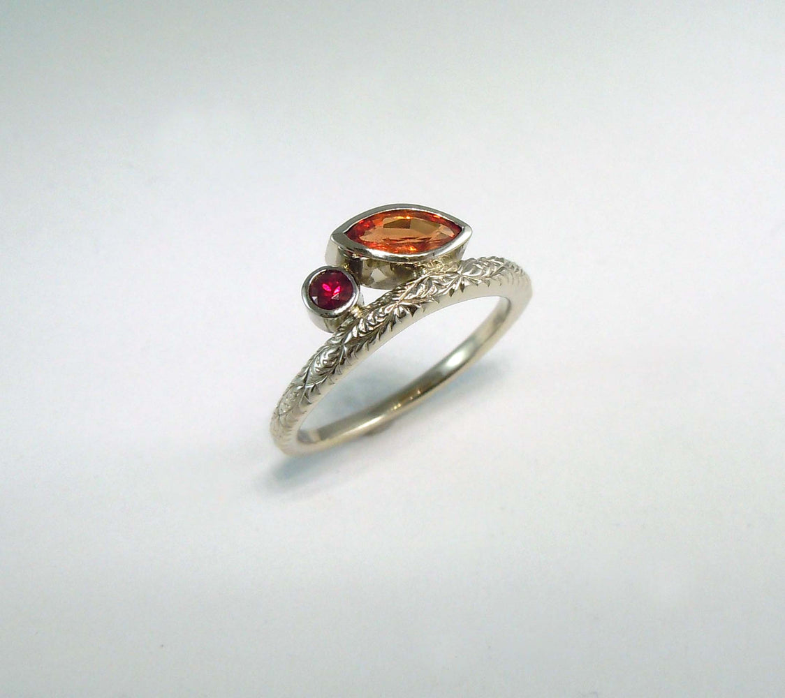 Delicate 14k white gold ring with an orange sapphire and a rudy.