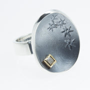 Unik Ring. A rough diamond cube set in 18k gold is placed on the uplifted edge of a dish of oxidized sterling silver balanced by a play of hand-engraved star flowers running along the opposite edge.  Size 5.25.