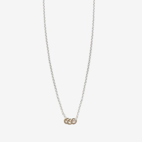 Delicate silver chain with three tiny 14k gold hoops.