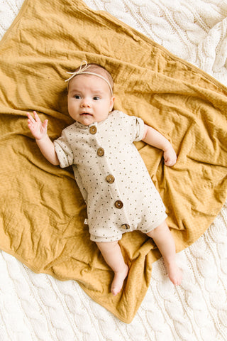 rolled sleeve romper in 'dots' on oatmeal