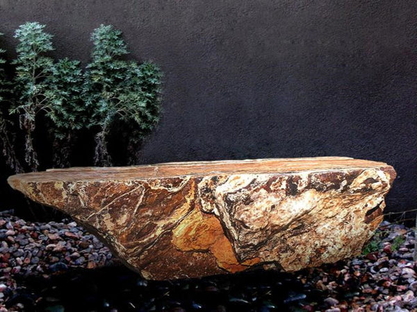 Black Canyon Onyx stone bench from The Rock Star Gallery in a garden courtyard landscape design.