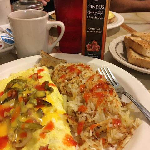 Denver omelette with hash browns and Gindo's Original Fresh & Spicy, a 7x award-winning Louisiana style hot sauce.