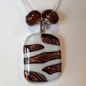 warm coloured dichroic on white striped pendant in fused glass with 2 amber glass beads