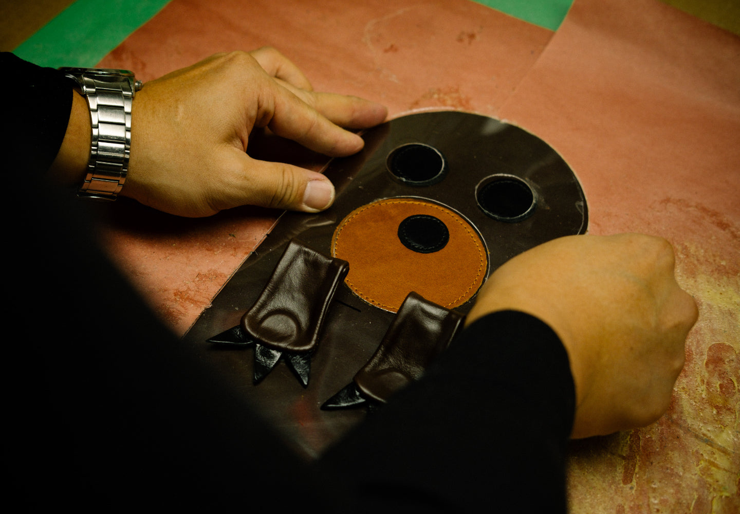 A photo of a craftsperson assembling a custom head cover