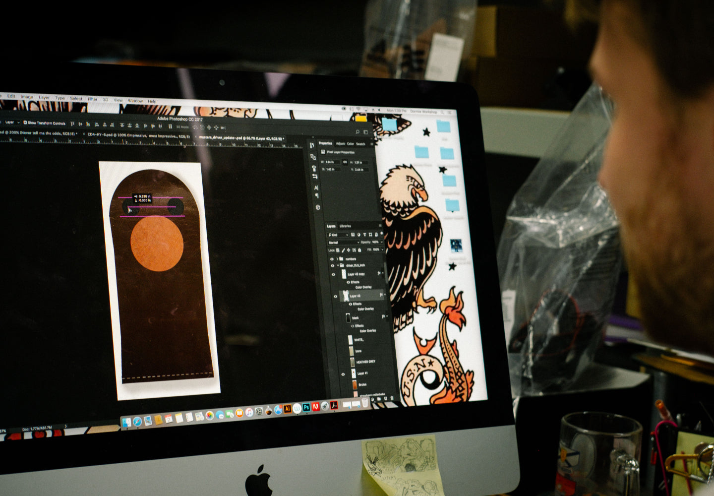Photo of designer looking at mockup of club head design on a computer screen
