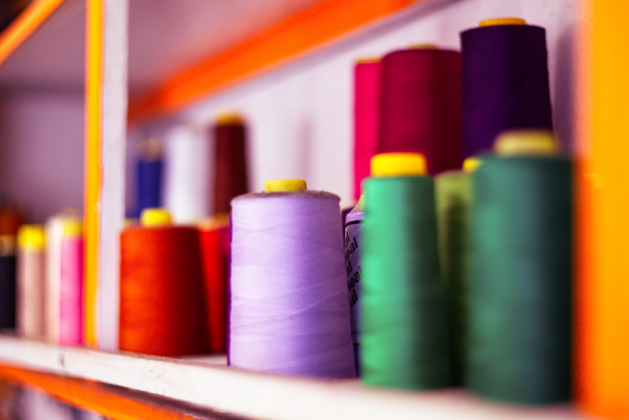 Photo of colourful thread on spools on a shelf