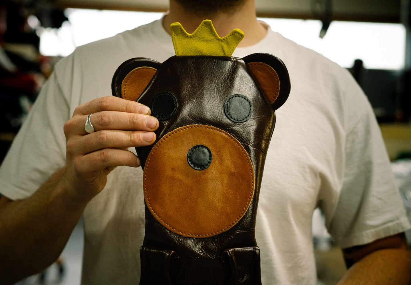 Photo of a fully-assembled custom club head cover being held up by a craftsperson