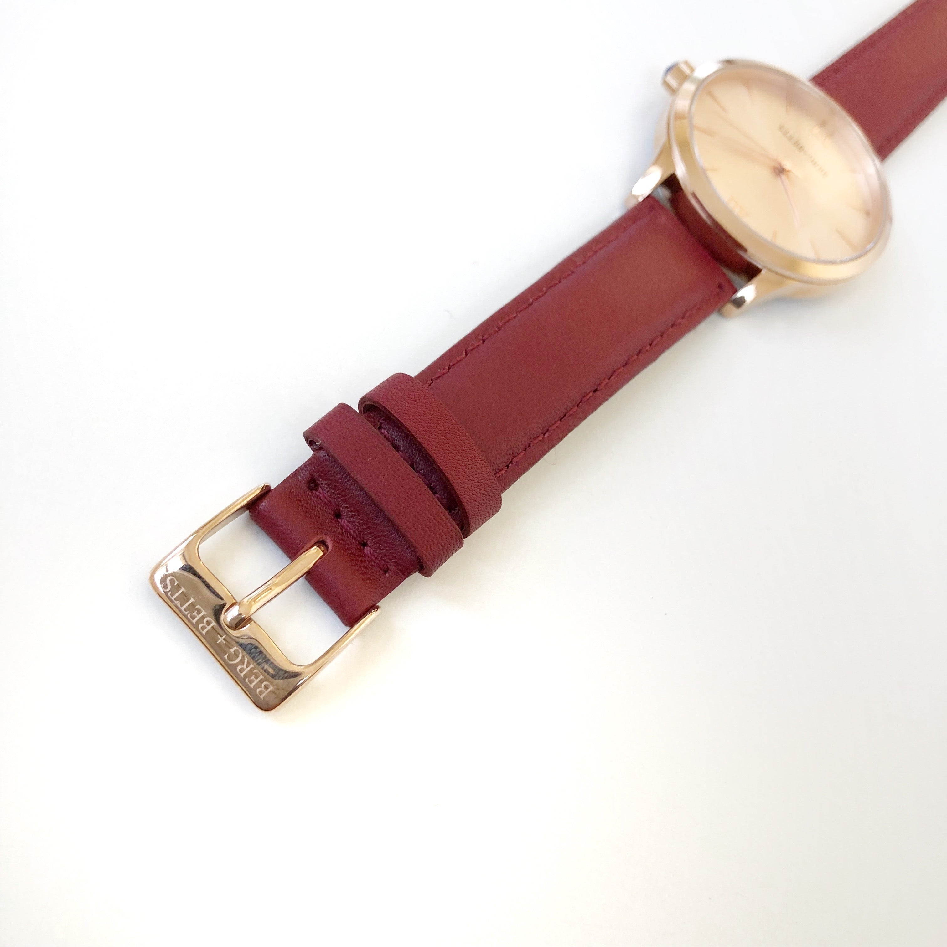 Minimalistic round rose gold watch ethically made with burgundy strap made from recycled leather
