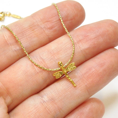 Gold plated delicate dragonfly insect pendant charm necklace, held for scale