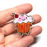 cupcake brooch with pink frosting on hand for size