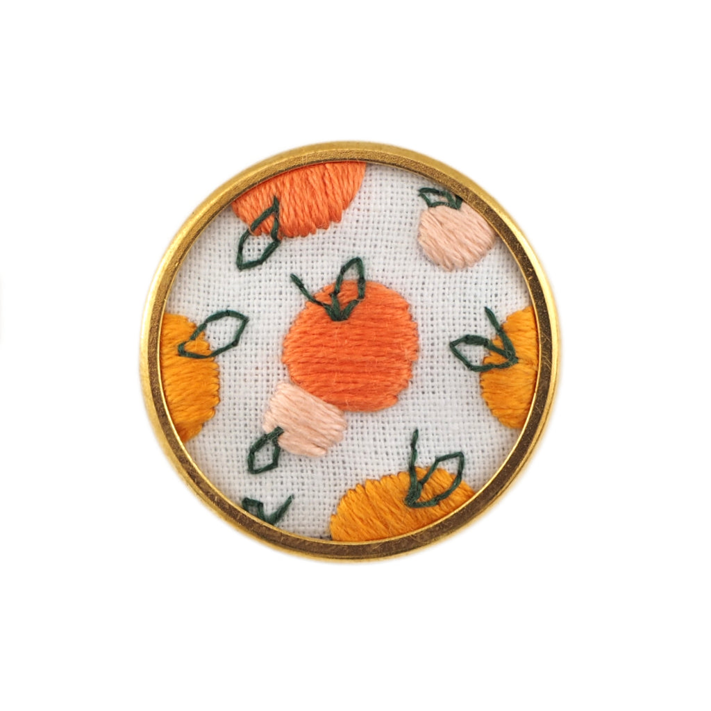 Peaches fruit embroidered pin - peach pattern on round white background