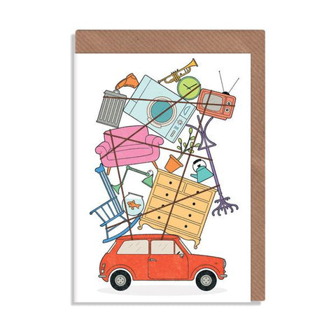 Housewarming card with pile of furniture and belongings tied to roof of a small red car.