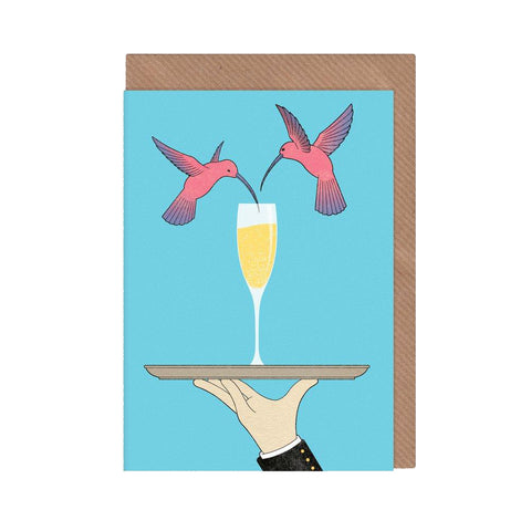 Celebration card with two pink hummingbirds and champagne on a blue background. With brown envelope.