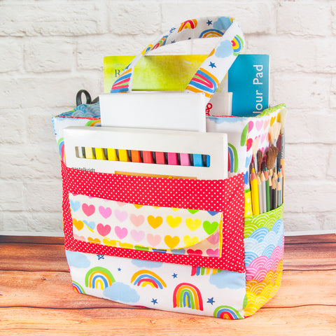 A fabric art caddy made with rainbow printed fabrics filled with pencils and crayons