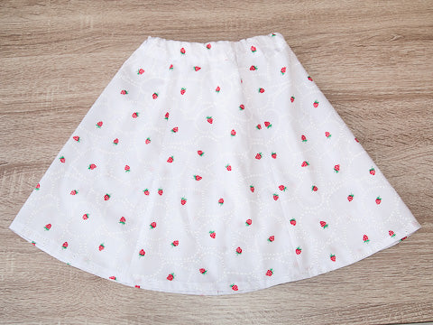 A girl's white summer skirt with little red strawberries and hearts laid out on table