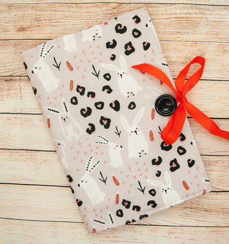 A notepad with a fabric covering made from beige rabbit printed fabric with an orange ribbon