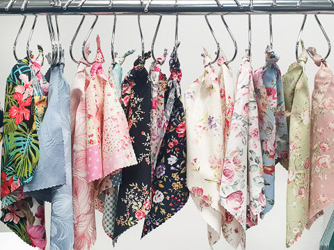 Fat quarters of floral cotton fabrics hanging on s hooks from a chrome rail