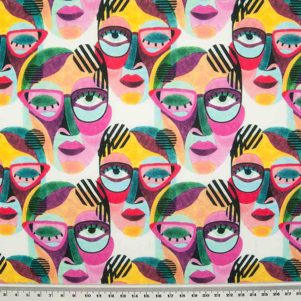 Abstract face paintings in vibrant pinks and greens are printed on a 100% cotton fabric by Little Johnny with a ruler for size perspective.