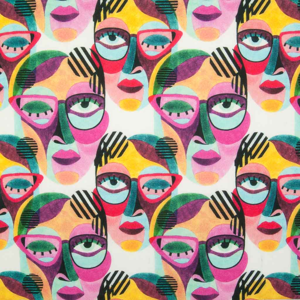 Abstract face paintings in vibrant pinks and greens are printed on a 100% cotton fabric by Little Johnny