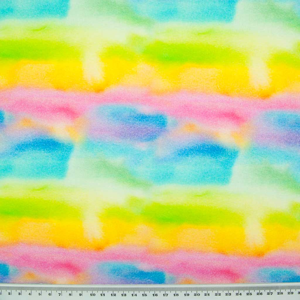 Bright colours of the rainbow are painted with watercolour on this 100% cotton fabric by Little Johnny with a ruler at the bottom for size perspective