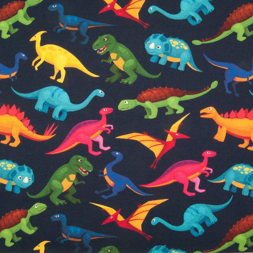 Various dinosaurs in green, pink, blue and yellow printed on a fat quarter piece of cotton jersey french terry fabric on a navy background